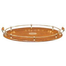 Oval mahogany tray with silver plate gallery and handles.