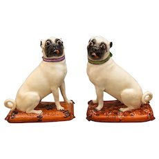 A rare Pair of Meissen Pugs on red Pillows