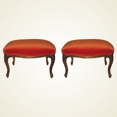 A pair of Victorian carved wood foot stools, newly upholstered in a rich orange velvet.