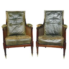 Pair Regency mahogany caned bergere chairs with fluted legs and uprights, and old leather squabs (England, c.1820)