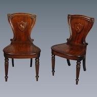 Pair of George IV mahogany hall chairs in the manner of Gillows, with a painted family crest. England, c.1820.