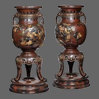 A pair of Meiji period rotating bronze and mixed metal vases