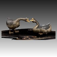 A Showa period okimono of two ducks on an original black lacquer stand with original box