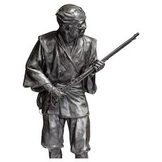 A Meiji period bronze of a huntsman carrying a gun