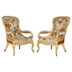 A pair of high Victorian gilt wood and needlework arm chairs by Gillows