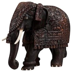 A large Indian carved hardwood elephant with bone tusks and toe nails, intricately carved throughout.