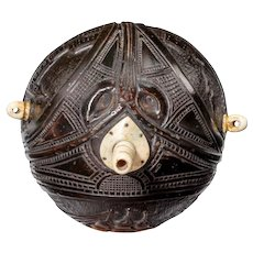 "A rounded coconut shell ""bugbear"" powder flask with a bone plug and handles"
