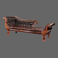 A William IV rosewood chaise longue attributed to Gillows, with deeply carved scroll terminals and arms.