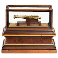 A miniature brass cannon in a presentation case