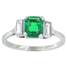 An Emerald And Diamond Three Stone Ring
