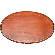 Oval mahogany tray with pierced brass gallery and handles.