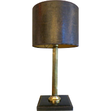 A hand-stitched leather based lamp with receded column stem and faux shade. In the manner of Adnet.