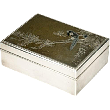 A Japanese silver box with an inlaid mixed metal panel.