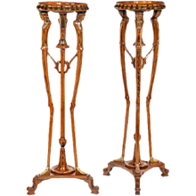 A pair of late Victorian painted satinwood and ormolu tripod stands