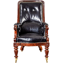 An early Victorian rosewood library chair, with a high back and scroll arms on turned tapering legs, with leather upholstery.